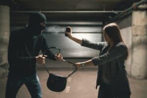 Woman using pepper spray for self defense against thief